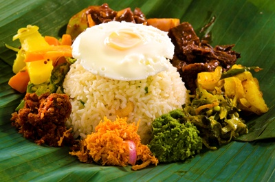 Lumprais:  rice with fried egg, roasted cashew nuts, vegetables and a deviled dish in banana leaf.