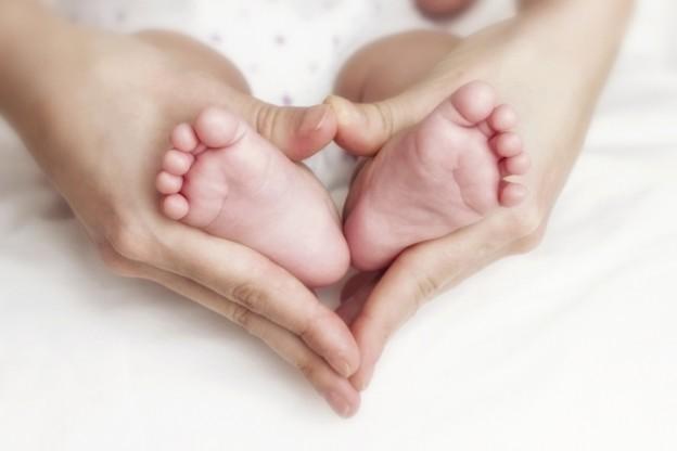 Newborn baby feet in the mother hands